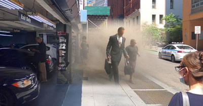 Augmented reality tech reveals people passing by a Beekman Street parking garage as they flee lower Manhattan through smoke and ash on September 11, 2001.